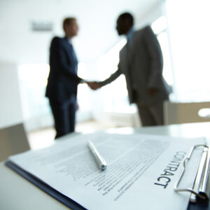 Image of business contract on background of two employees handsh